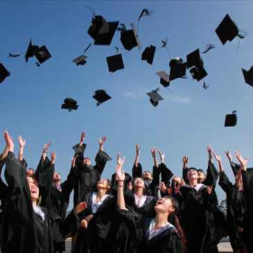 graduate students flying caps